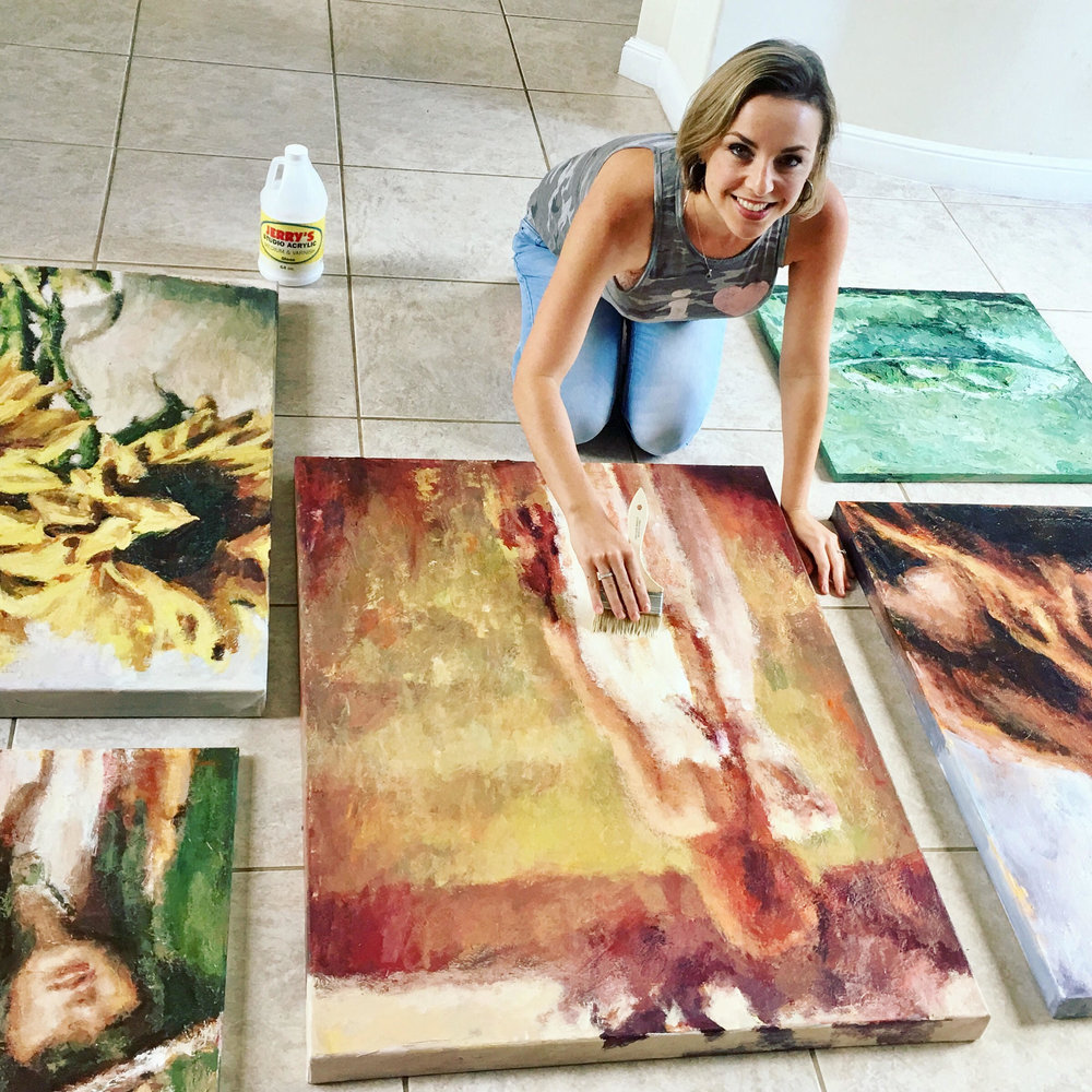 Artist Nava Lundy varnishing her paintings