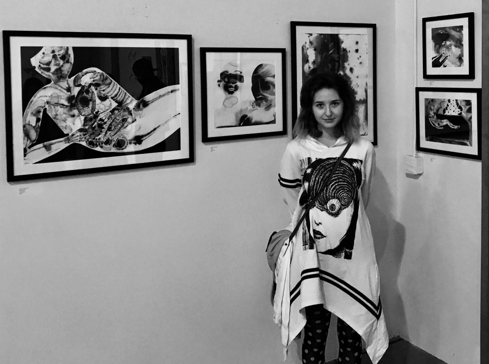 Annalise LaFlamme  photographed in front of her artwork.