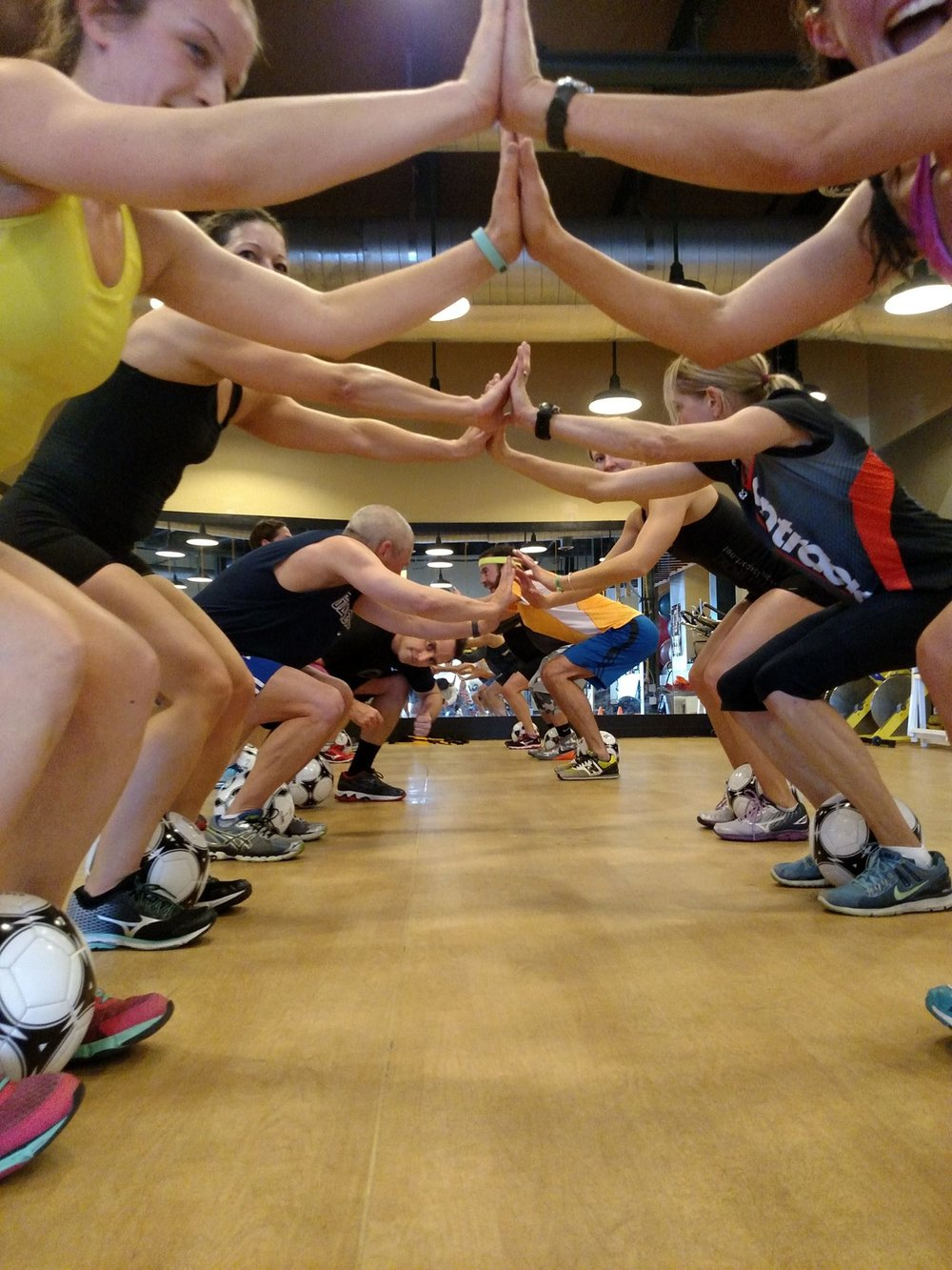 People forming tunnel with hands during a fitness class