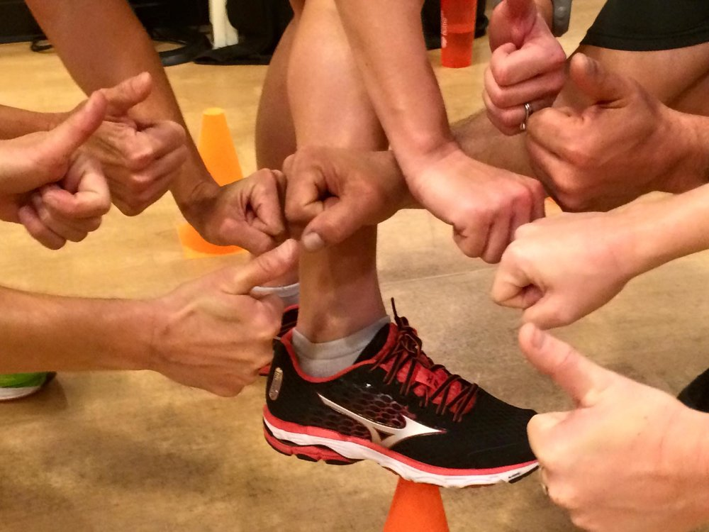 People's hands clustered into a circle giving thumbs up after a fitness class