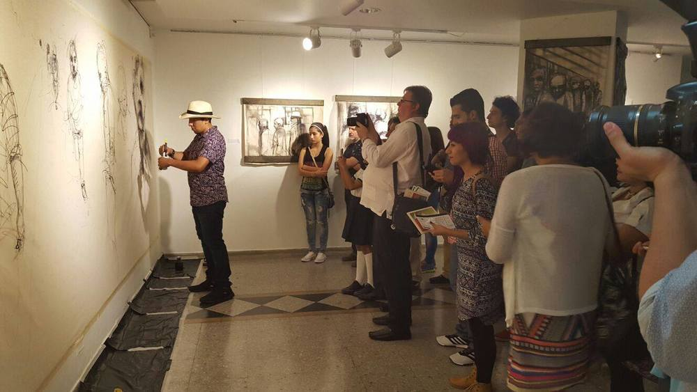 Toronto artist painting live in front of a gallery crowd in Pereira, Colombia