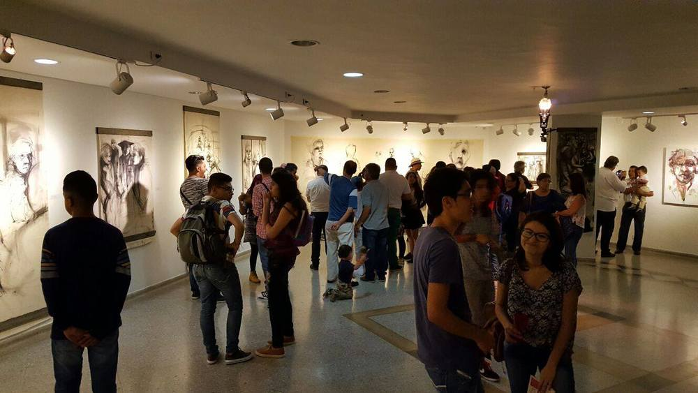 People gather to view contemporary and abstract art in Sala Carlos Drew Castro in Instituto de Cultura y Fomento al Turismo in Colombia