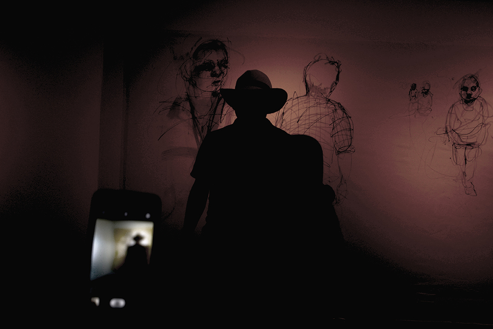 Lights, phones and red hues to highlight the artist Carlos Delgado in his solo art show.