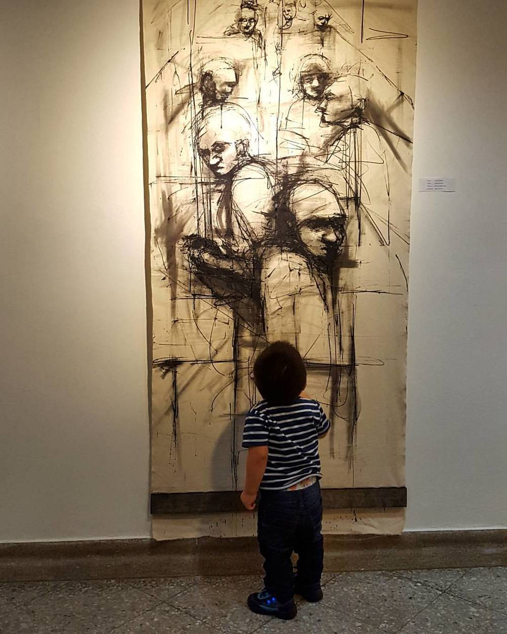 Children gazing upon an art painting inside a gallery by Carlos Delgado