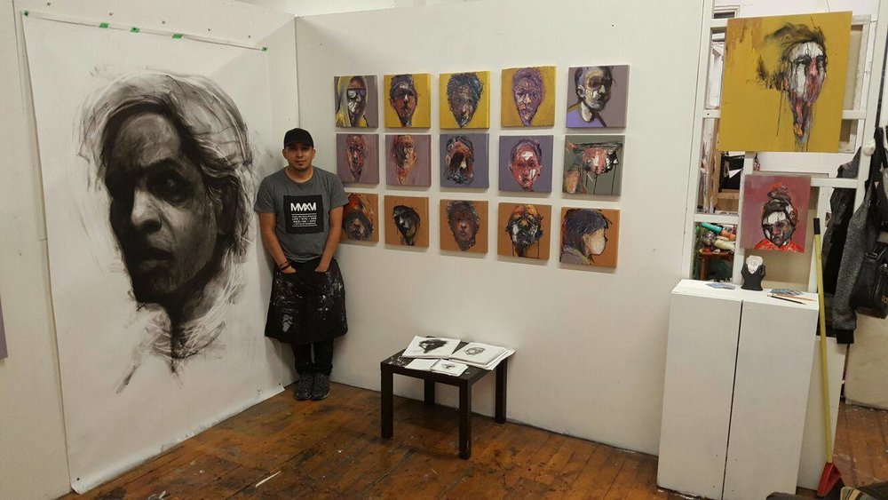 Mini composition of abstract portrait original paintings by Carlos Delgado and large scale charcoal drawings in Toronto art studio.