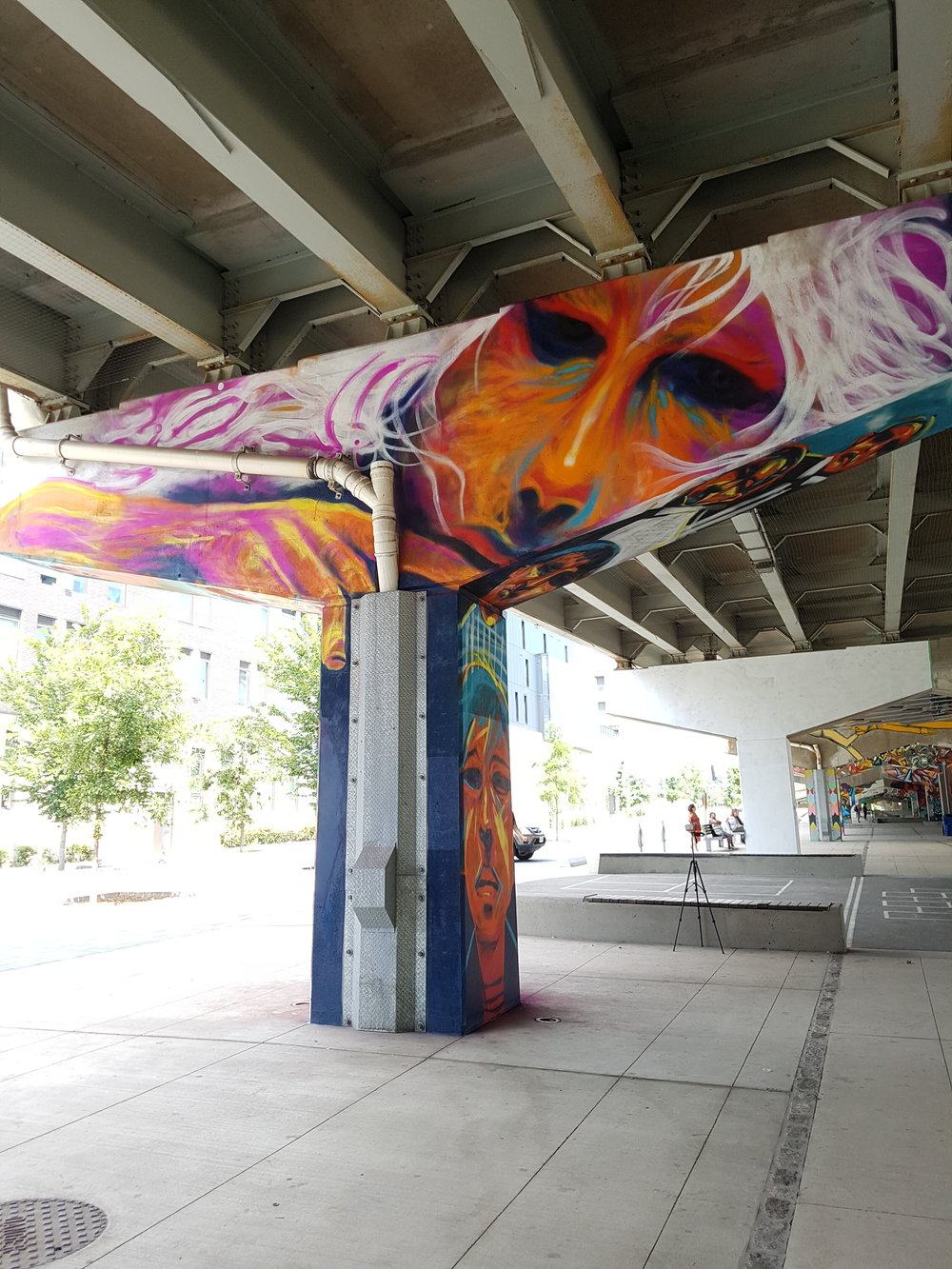 Back of mural in Underpass Park, abstract faces decorate the column.