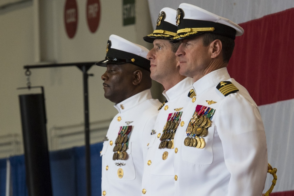(From the left) Command Master Chief USS Harry S. Truman (CVN 75), Command Master Chief Antonio Perryman; Incoming commanding officer, USS Harry S. Truman, Capt. Nicolas Dienna and Off-going Commanding Officer, USS Harry S. Truman, Capt. Ryan B. Scholl stand at attention while sailors parade the colors during the Truman change of command ceremony in the ship's hangar bay. Truman hosted a change of command on the 19th anniversary week of the ship's commissioning. (U.S. Navy photo by Mass Communication Specialist Seaman Kaysee Lohmann/Released)