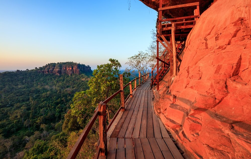 wooden bridge path up a red mountain to a temple in Thailand