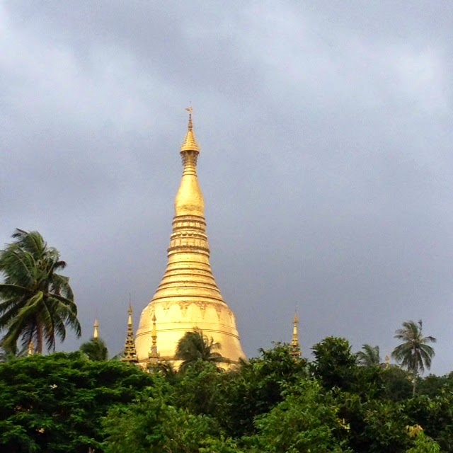 golden pagoda over the green jungle against grey sky