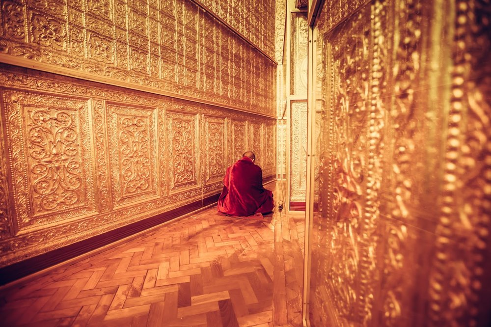 red robed monk sits and meditates inside golden Botataung pagoda