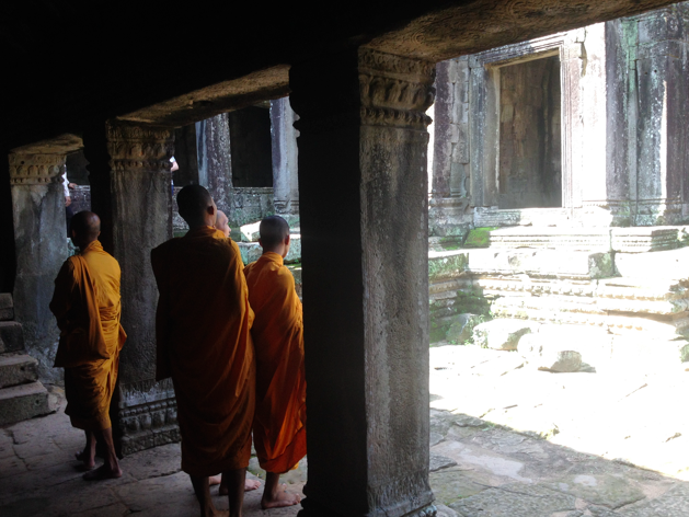 monks in orange  robes in ancient stone temple angkor wat cambodia