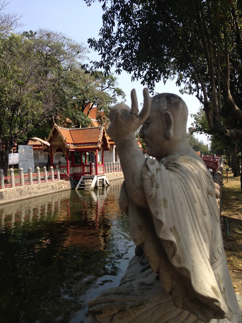 statue of a monk by a fish pond on the grounds of the Marble Temple in Bangkok, Thailand
