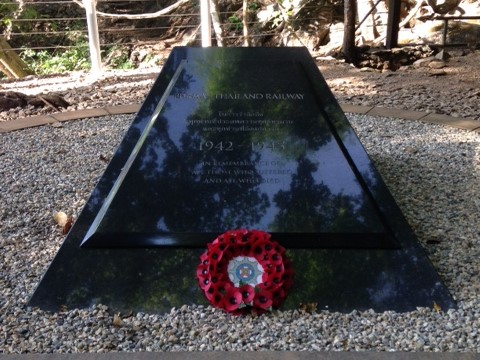 black stone memorial with red poppy wreath to remember POWs of the Thai-Burmese Death Railway in Hellfire Pass, Kanchanaburi, Thailand