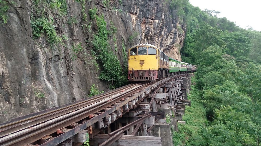 raised trestle bridge built into the cliffside with old train riding along wang po viaduct of the Thai-Burmese Death Railway in Kanchanaburi, Thailand