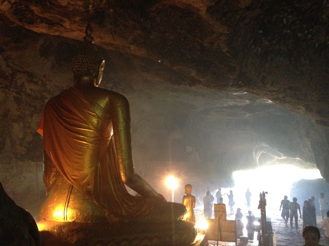 seated golden buddha looking out of a cave in Kanchanaburi, Thailand