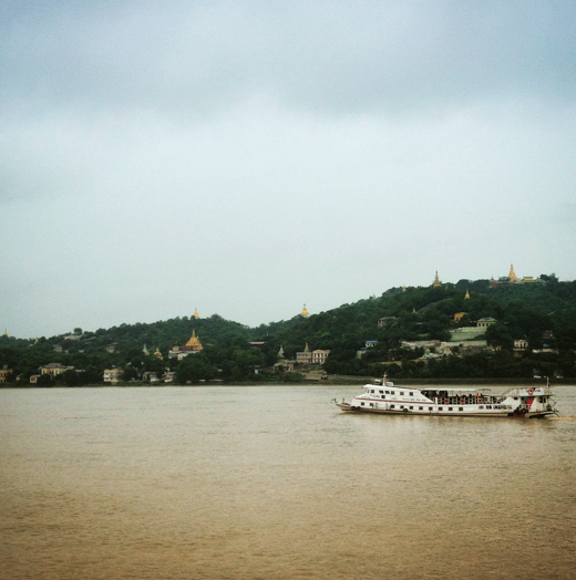 a boat cruises the irawaddy river in myanmar past a hill covered  with temples