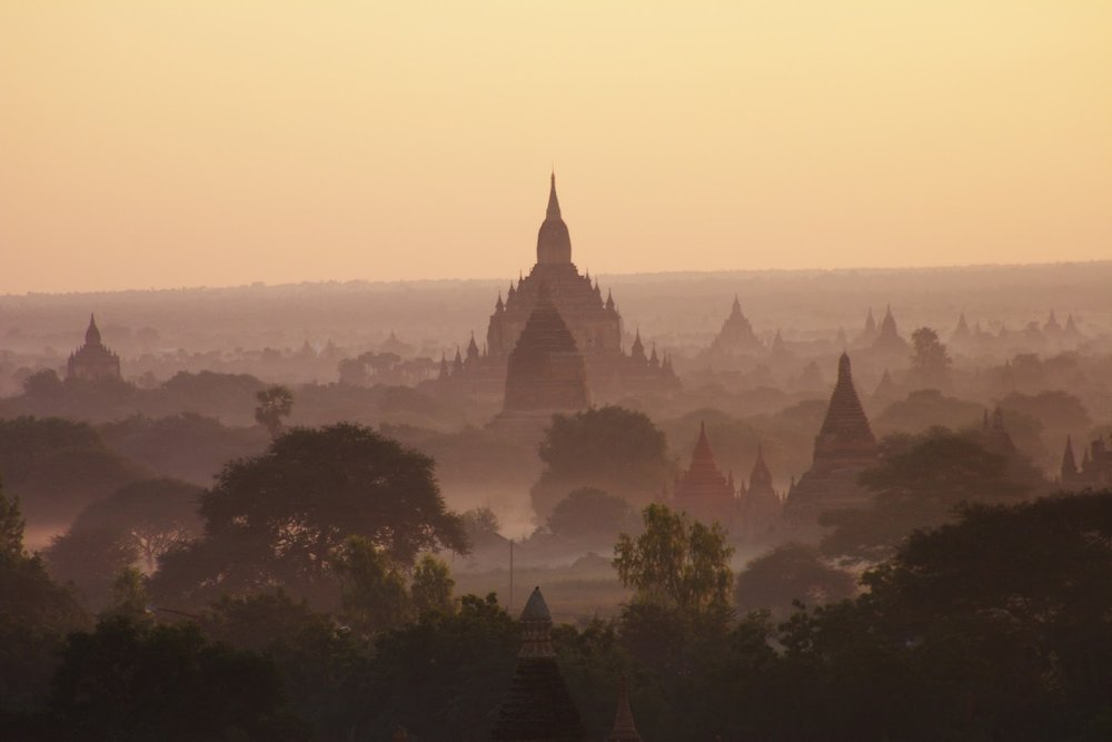 a misty early morning in Bagan, myanmar, with dozens of small stone temples in a field