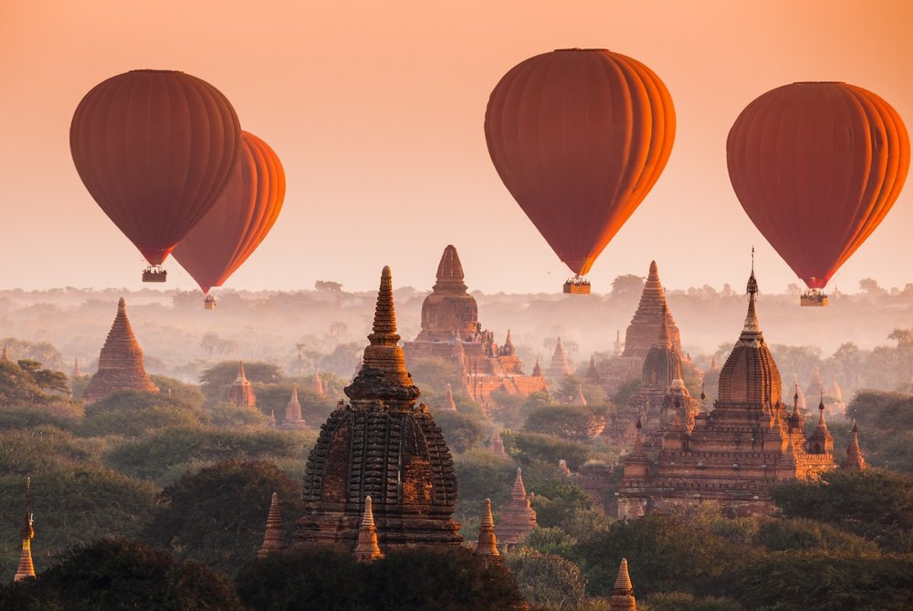 hot air balloons in Bagan myanmar over a field of stone temples at sunrise