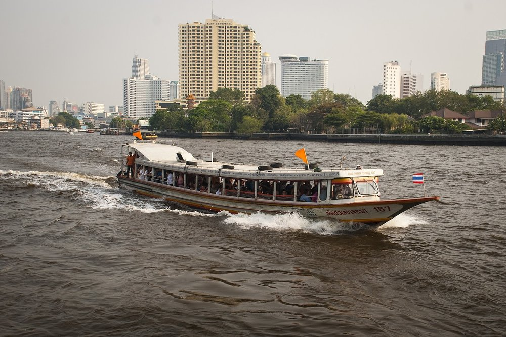 an orange flag tourist boat on the chaophraya river in Bangkok, Thailand