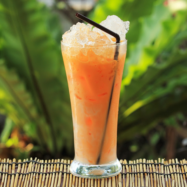 a glass of orange Thai iced tea