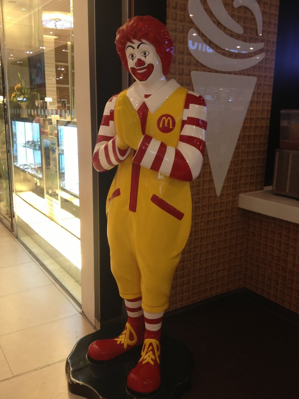 Ronald  McDonald statue giving a traditional Thai wai (greeting, bow) in front of a McDonalds restaurant chain in downtown Bangkok, Thailand