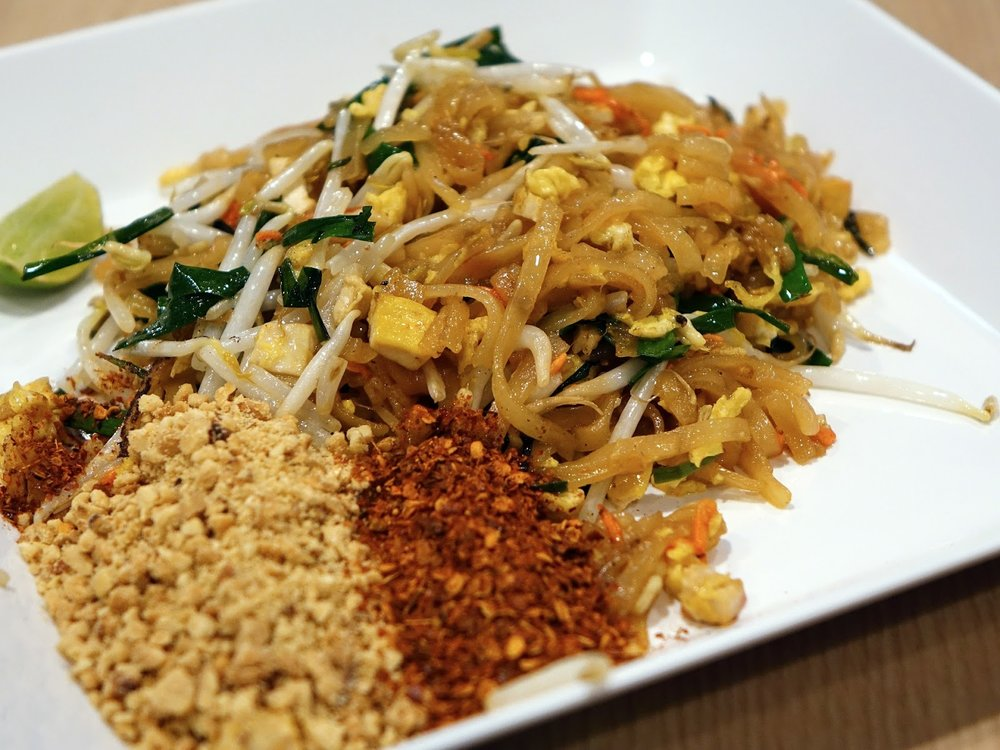 a dish of Pad Thai served on a white plate with peanut and red chili flakes