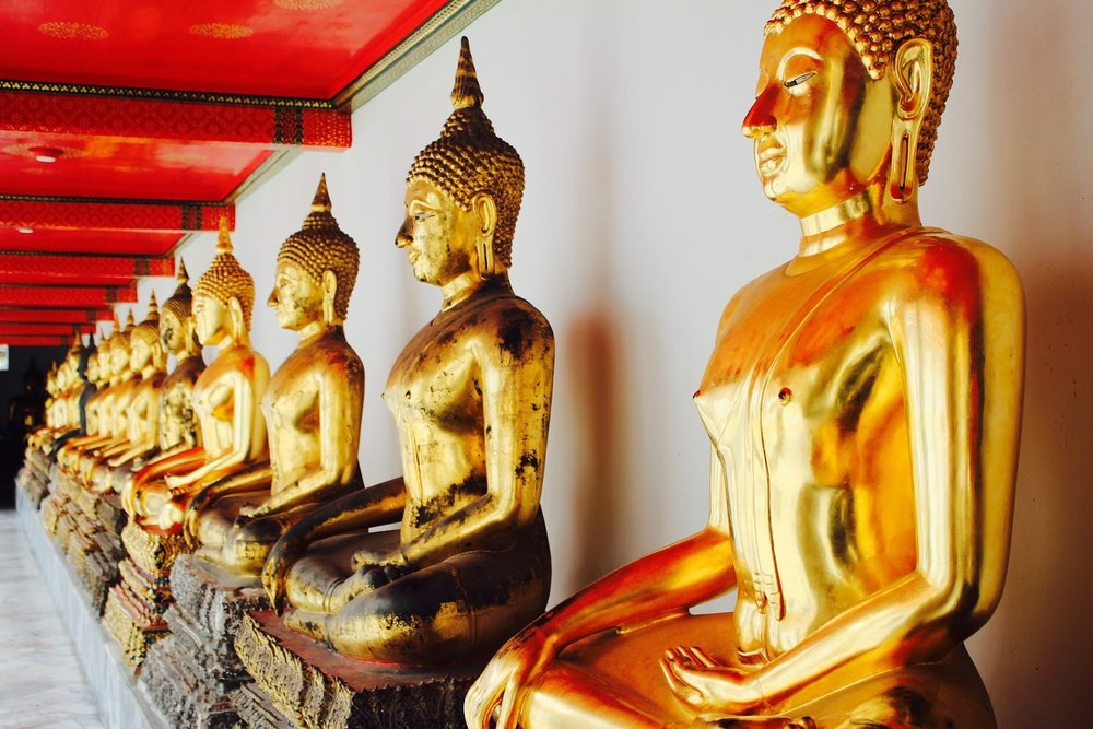 a row of golden seated Buddha statues at a temple in Bangkok, Thailand
