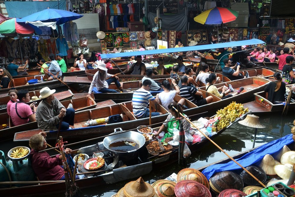 a busy floating market with vendors and tourists in Thailand