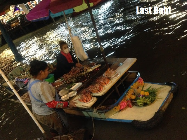 grileld fish served from a boat at Ampawah floating market, Thailand