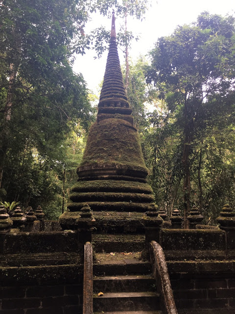 a stone chedi covered in moss in Thailand