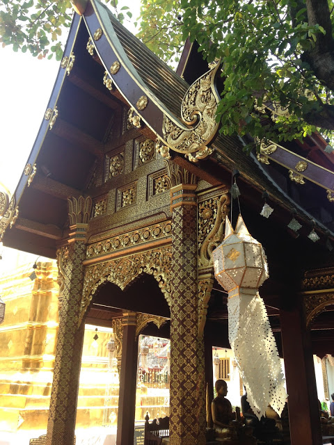 a wooden shrine building houses Buddha statues at a temple in Chiang Mai, Thailand