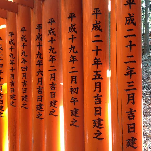 black kanji characters on the red torii gates at fushimi inari in Kyoto, Japan