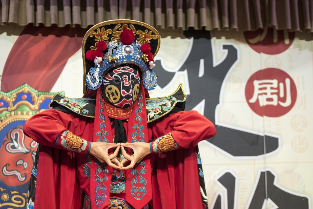 traditional Chinese opera performer in red with a mask