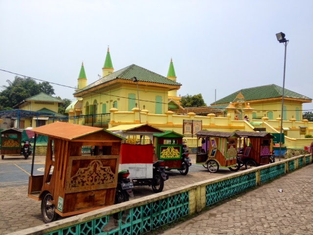 a row of wooden carriages waits outside a brighe yellow masjid on Penyengat Island, Indonesia