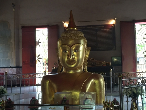 a half-buried golden Buddha head and torso at Wat Prathong, Phuket, Thailand