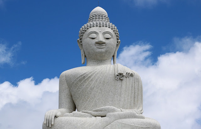 a large white alabaster statue of the Buddha in a serene pose against a blue sky in Phuket, Thailand