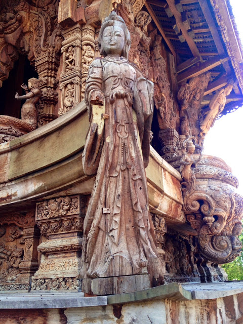 a hand-carved wooden statue of the Chinese goddess Guanyin at a wooden temple in Pattaya, Thailand