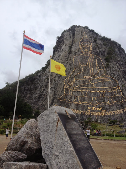 a golden Buddha image carved into the side of a mountain in Pattaya, Thailand