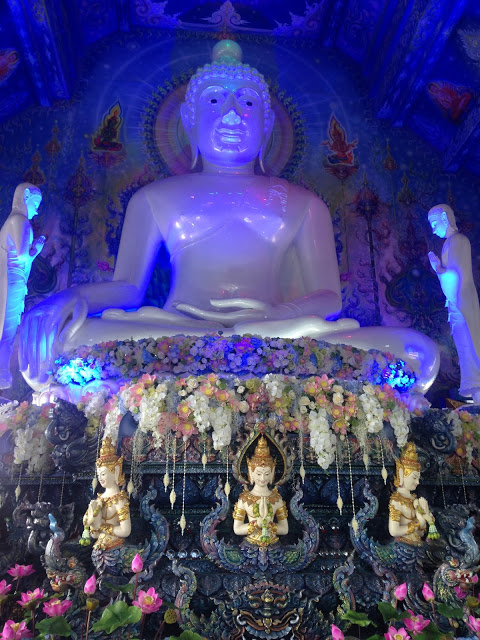 white marble buddha statue seated in blue light temple chiang mai thailand