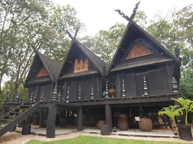 three wooden black buildings chiang rai thailand
