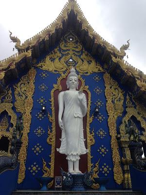 white marble standing buddha statue blue temple chiang rai thailand