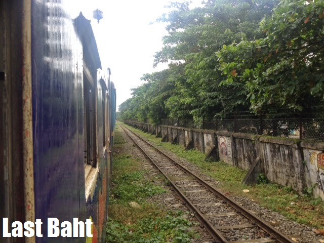 a blue train slowly moves through Yangon (Rangoon) Burma