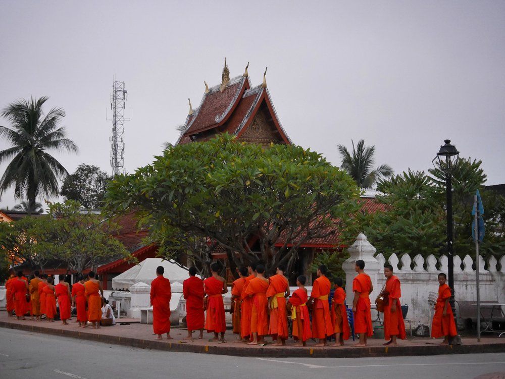 monks in front of Wat Mai on their morning alms rounds in Luang Prabang, Laos