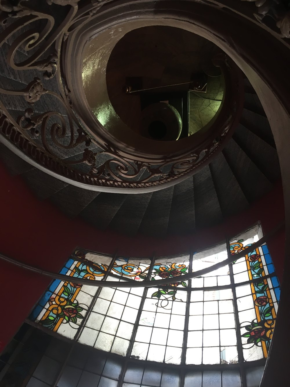 a spiral staircase and stained glass window inside the Museum of Fine Arts