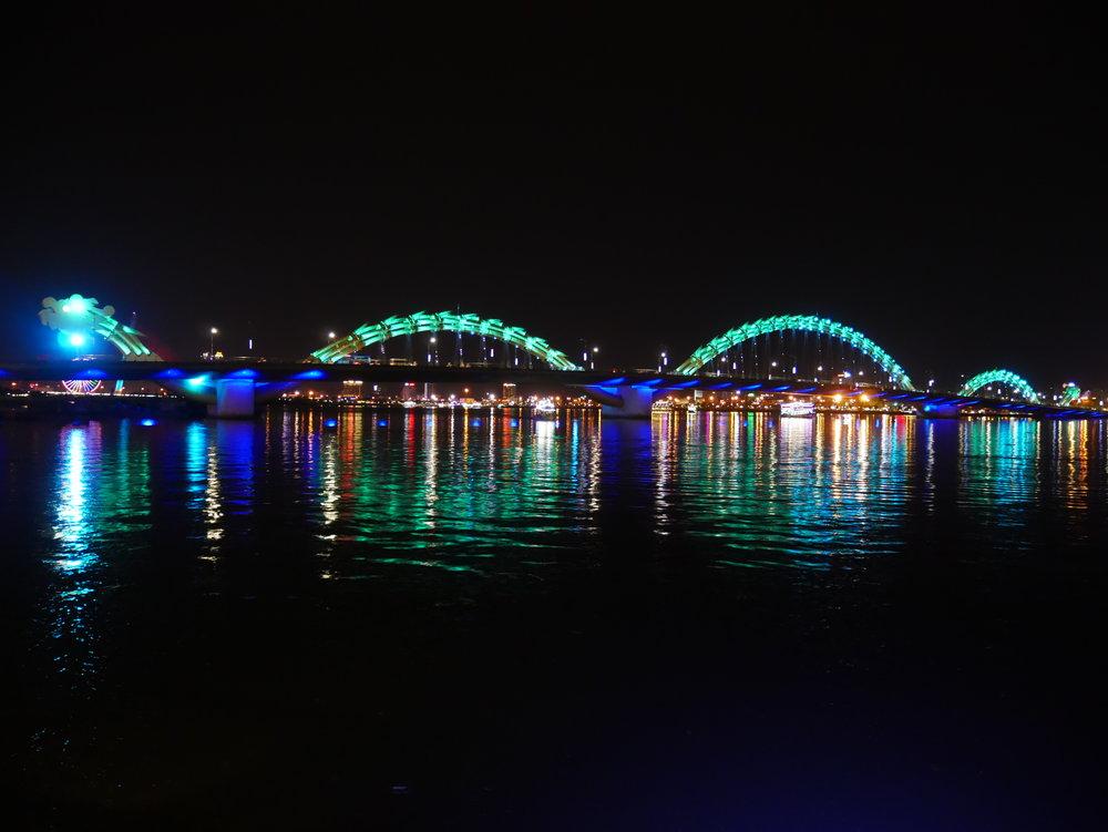Dragon Bridge in Da Nang lit up with colorful lights at nighttime