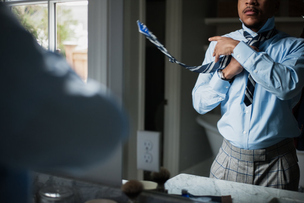 tying a custom blue tie on a custom blue shirt by stitch it shirt