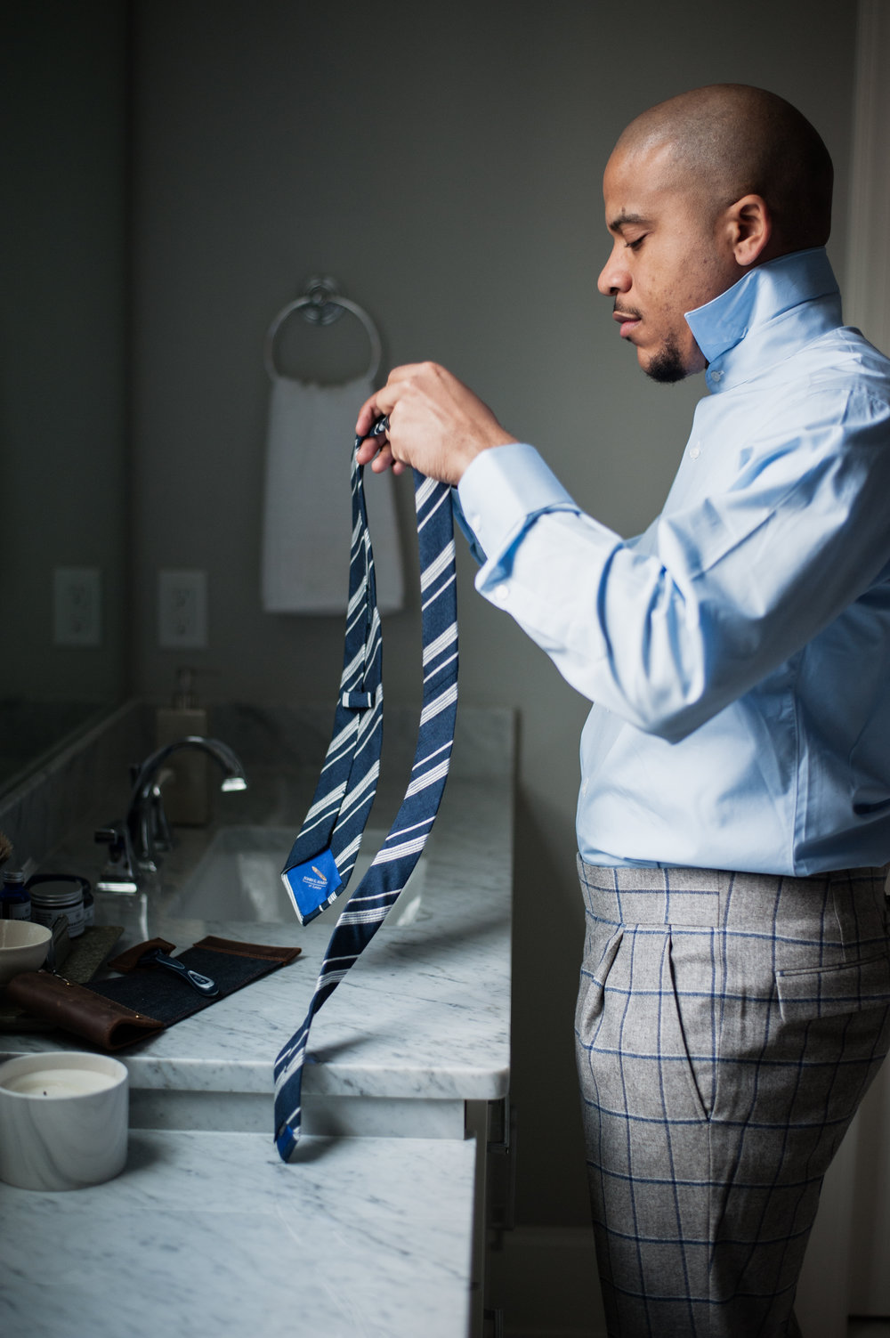 examining custom blue striped tie