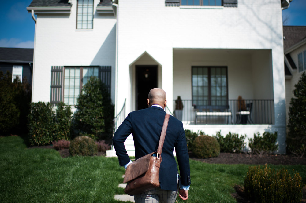 blue custom suit, leather side bag facing white brick house in Nashville