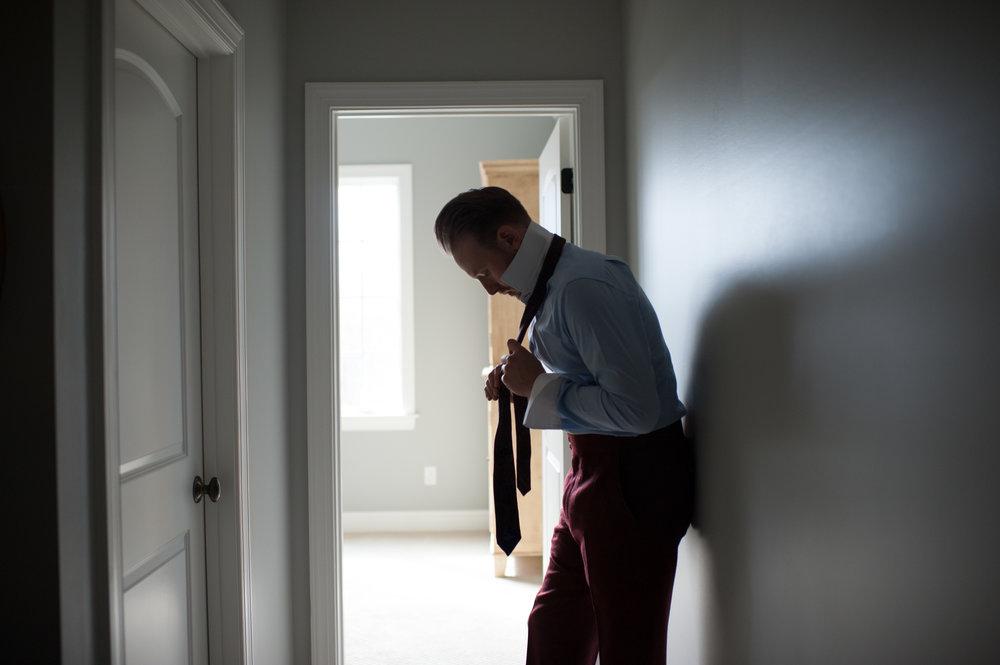 tying maroon bespoke tie with bespoke suit