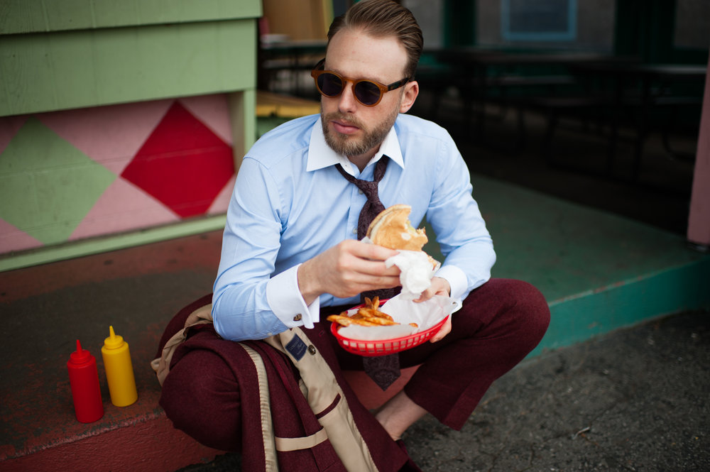man in bespoke suit eating a Nashville burger.jpg